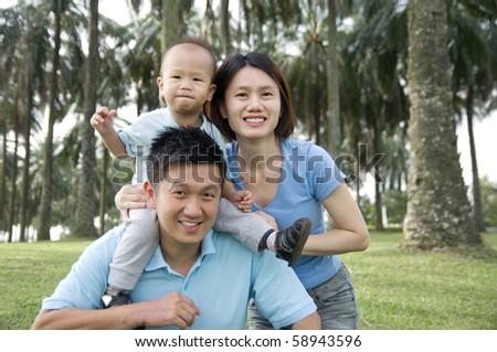 Asian family having fun in the park - stock photo