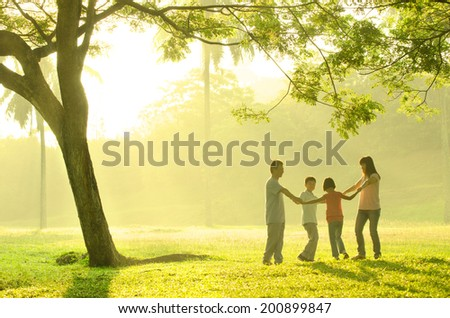 asian family having quality time playing together in the park - stock photo