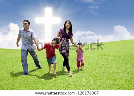 Asian family is having a stroll in a park by the Cross - stock photo