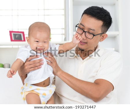 Asian family lifestyle at home. Father playing with his baby boy. - stock photo