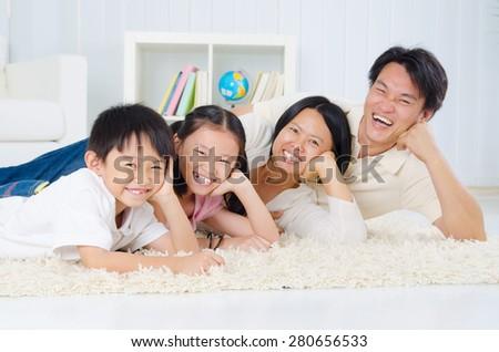 Asian family lying on the floor - stock photo