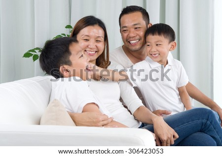 Asian family playing on sofa - stock photo