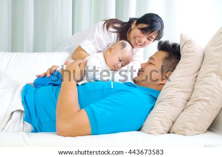 Asian family playing with their baby - stock photo