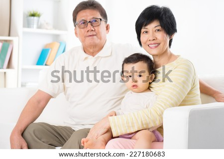 Asian family portrait, relaxing at home, grandparents and grandchild living lifestyle indoor. - stock photo