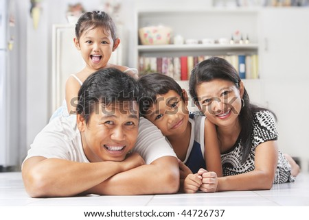 Asian family posing on the floor at home - stock photo
