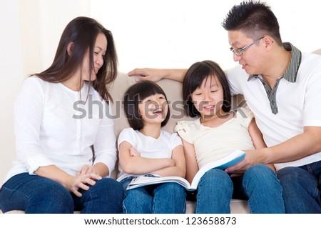 Asian family reading at home - stock photo