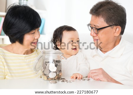 Asian family saving money indoor, financial concept, grandparents and grandchild living lifestyle at home. - stock photo