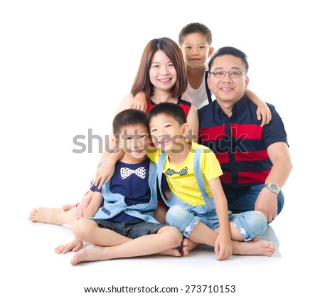 Asian family sitting on the floor - stock photo