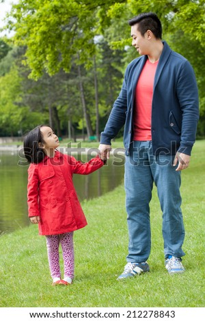 Asian family walking in a park, vertical - stock photo