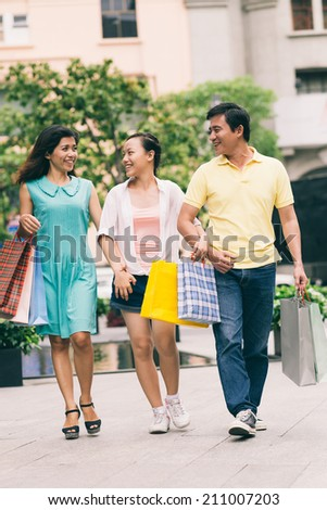 Asian family walking in the city with purchases in hands - stock photo