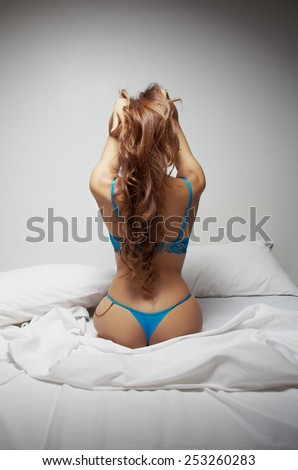 Asian fashion model in lingerie in desire on the white sheet - stock photo
