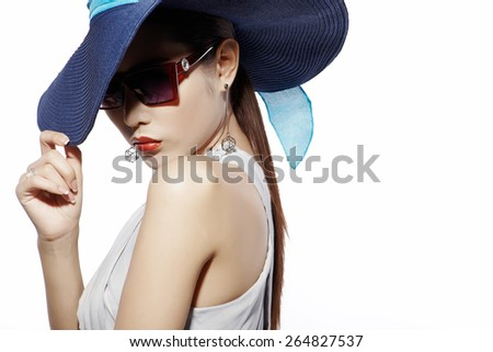 Asian fashion model in sunglasses and hat against white background - stock photo