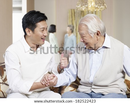 asian father and adult son chatting on couch - stock photo