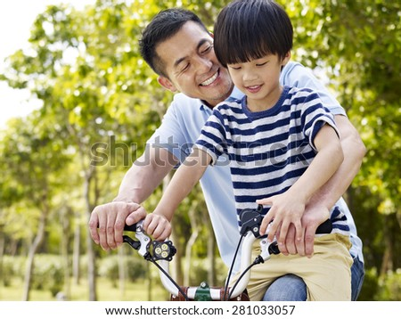 asian father and elementary-age son enjoying riding a bike outdoors in a park. - stock photo