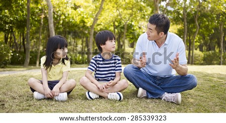asian father and two children sitting on grass having an interesting conversation, outdoors in a park. - stock photo