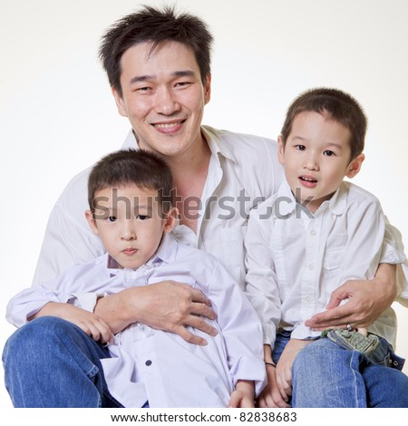 Asian father with two sons on white background - stock photo