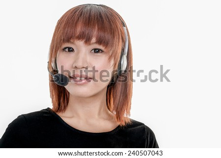 Asian female call center operator wearing a headset with microphone, looking at camera - stock photo