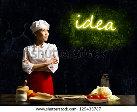 Asian female chef looking at the glowing title idea, place for text - stock photo