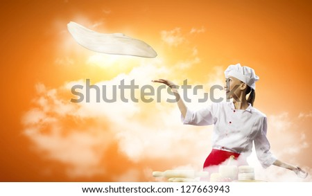 Asian female cook making pizza standing against color background - stock photo