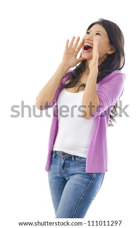 Asian female holding hands beside her cheeks and shouts an announcement. - stock photo