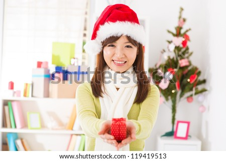 Asian female in santa hat giving a Christmas gift - stock photo