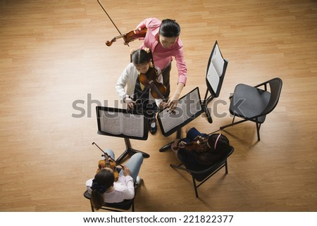 Asian female music teacher helping student play violin - stock photo