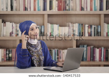 Asian female muslim thinking at library in blue dress - stock photo