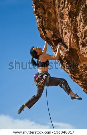 Asian female rock climber struggles for her next grip on a challenging ascent. - stock photo
