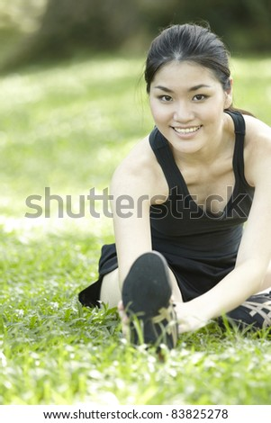 Asian female runner stretching before exercising. - stock photo