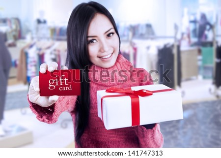 Asian female shopper showing gift card and box at the mall - stock photo