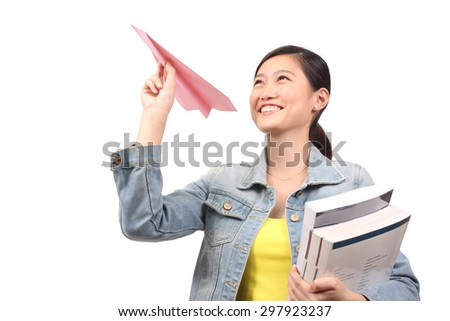 Asian female student holding books and paper aeroplane - stock photo