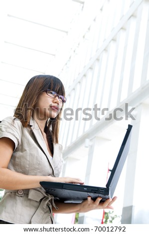 Asian female with laptop outside a modern building - stock photo
