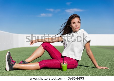 Asian fitness model in summer outdoors sitting on outdoor grass gym drinking a healthy green smoothie juice detox diet. Active living concept. Sporty woman athlete enjoying health. - stock photo