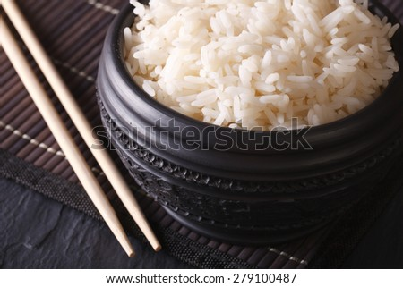 Asian food: boiled rice in a black bowl macro and chopsticks. horizontal   - stock photo