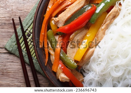 Asian food chicken with vegetables and rice noodles macro with chopsticks on the table. horizontal top view  - stock photo