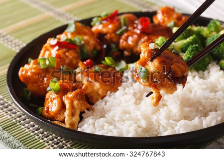 Asian food: General Tso's chicken with rice for dinner. Horizontal close-up - stock photo