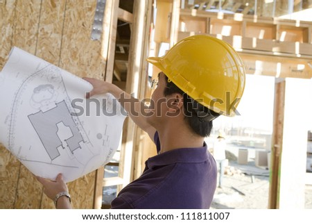 Asian foreman holding blueprint at construction site - stock photo