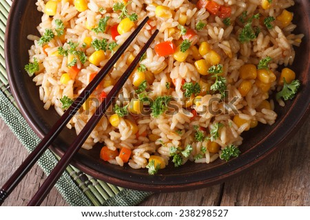 Asian fried rice with corn and eggs close-up on a plate, horizontal view from above  - stock photo