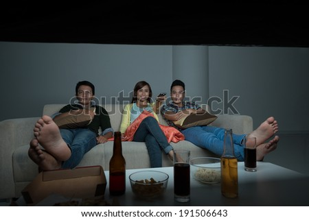 Asian friends watching tv show at home - stock photo