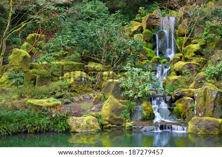 Asian Garden Waterfall flowing into a still pond surrounded by moss covered rocks, trees, and other foliage - stock photo