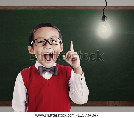 Asian genius student with light bulb shot in a classroom - stock photo