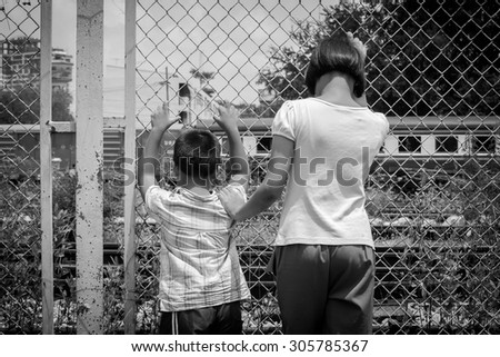 asian girl and boy sad  hand hold jail at Railroad,railway station,black and white tone - stock photo