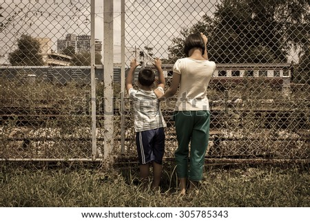 asian girl and boy sad  hand hold jail at Railroad,railway station,vintage tone - stock photo
