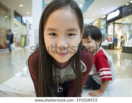 asian girl and  boy smiling at the shopping mall - stock photo