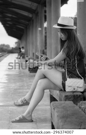 Asian girl at the railway station waiting for a train in black and white - stock photo