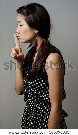 Asian girl doing a secret sign - stock photo