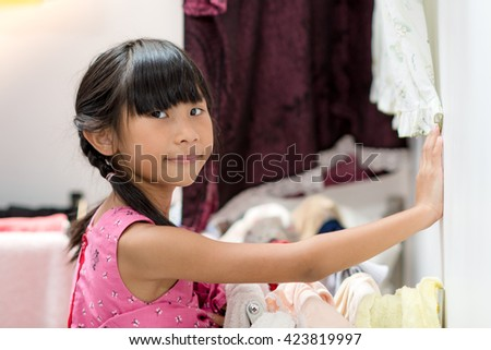 Asian girl doing laundry at home - stock photo