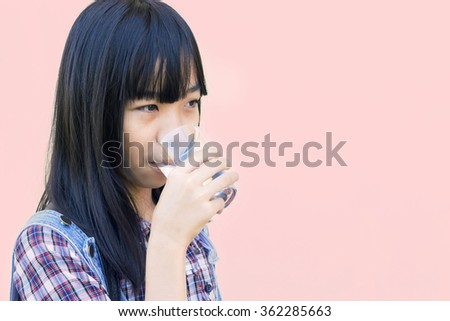 Asian girl drinking water from glass - stock photo