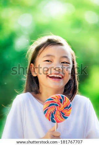 Asian girl eating a colorful candy with green nature background. - stock photo