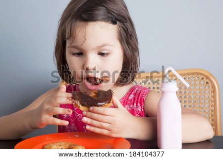 Asian girl eating a donut with milk - stock photo